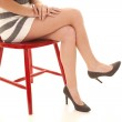 Woman legs skirt red chair — Stock Photo