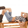 Cowgirl lay back on bench smile — Stock Photo #27056651