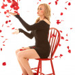 Woman blowing rose pedals sitting — Stock Photo