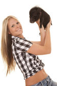 Woman hold up pig look smile — Stock Photo