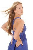 Woman blue dress wind side hands hips — Stock Photo