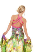 Woman colorful dress back hold sides — Stock Photo