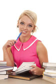 Woman in pink shirt books look pen — Stock Photo