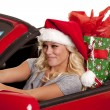 Woman santa hat car gift drive — ストック写真