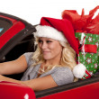 Woman santa hat car gift drive — Stock Photo