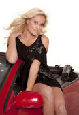 Woman black dress sit on door car — Stock Photo