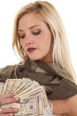 Woman holding money by heart looking at it — Stock Photo