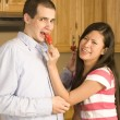 Wife feeding her husband a red pepper — Stock Photo