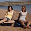 Stock Photo: Women sitting and relaxing on their towles on the beach