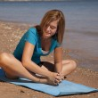 Woman stretching on the beach. — Stock Photo