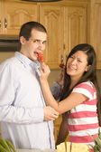 Marido de mulher alimentando uma pimenta vermelha — Foto Stock