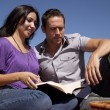 Couple outside reading book — Stockfoto