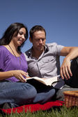 Couple outside reading book — Stock fotografie