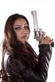Woman holding gun looking back — Stock Photo