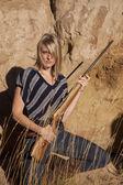 Woman in gras holding gun — Stock Photo