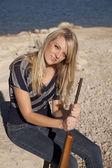 Woman lake rifle sit — 图库照片
