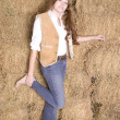 Stock Photo: Woman by hay stack leg up