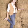 Woman by hay stack leg up — Stock Photo