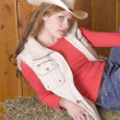 Woman in red shirt vest and hat on hay — Stock Photo
