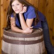 Woman leaning on barrel serious — Stock fotografie