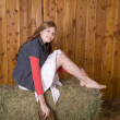 Woman on hay holding boots — Stock Photo
