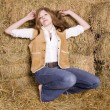 Woman posing by hay stack — Stock Photo
