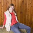 Woman sitting on hay in red shirt — Stock Photo
