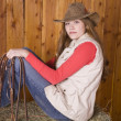 Womsitting on hay with bridle — Stock Photo #29580837