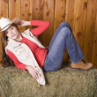Woman with red shirt and hat on hay — Stock Photo