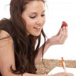 Woman eat strawberry homework writing. — Stock Photo