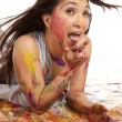 Laying in paint mouth and finger — Stock Photo