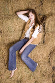 Woman posing sitting on haystack — Stockfoto