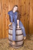 Woman sitting on barrel with a smile — Stock Photo