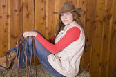 Woman sitting on hay with bridle — Stock Photo