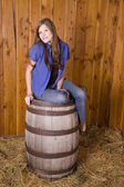 Woman smiling while sitting on barrel — Stock Photo