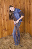 Woman standing with bridle on hip — Stock Photo