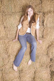 Woman sitting on haystack serious — Stock Photo