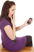 Woman in purple back shocked at phone screen — Stock Photo