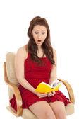 Kobieta czerwona sukienka książki siedzieć szoku — Zdjęcie stockowe