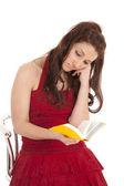 žena červené šaty znuděný čtení — Stock fotografie