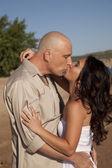 Couple kissing beach white dress — Stock Photo