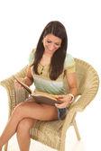 Mujer en la sonrisa de lectura de silla de mimbre mira hacia abajo — Foto de Stock