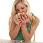Woman stuffing doughnuts onto mouth — Stock Photo