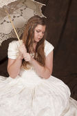 Girl white dress umbrella sit look down — Stock Photo