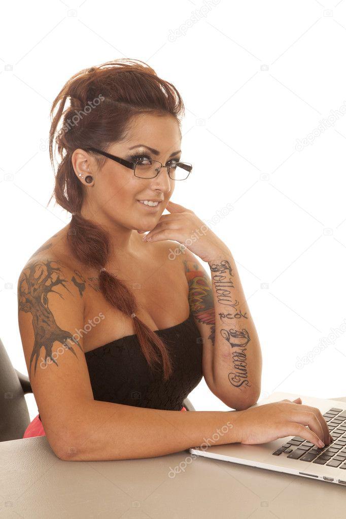 女人的纹身电脑边微笑