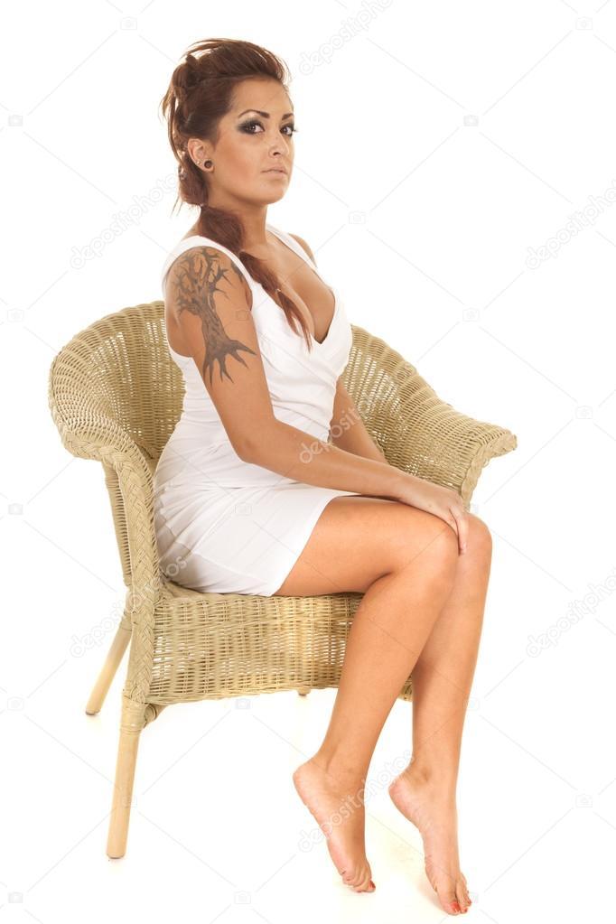Woman tattoos sit wicker chair side legs stock photo