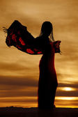 Woman silhouette blowing sarong — Stock Photo