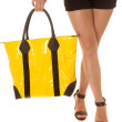 Woman legs yellow bag hold legs crossed — Stock Photo #31515045