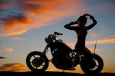 Silhouette of woman motorcycle sit backwards hands up — Stock Photo