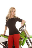 Woman red pants green motorcycle stand front close serious — Stock Photo